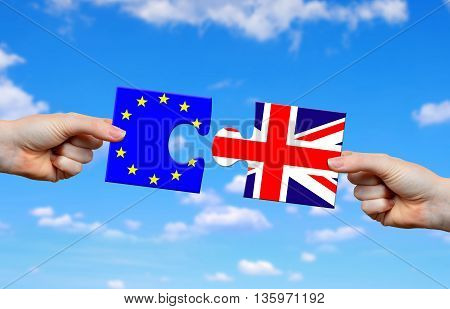 Brexit concept. Hands holding puzzle with flag of the UK and EU.