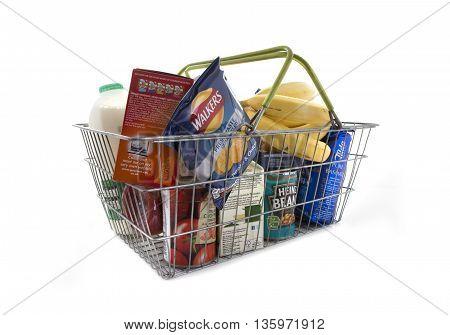 SWINDON UK - JUNE 26 2016: Shopping basket full of food including fresh fruit vegetables indicating a weekly family shop