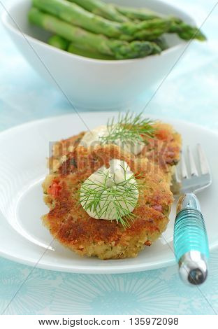 Fresh home made crab cakes with creamy lemon dill sauce and asparagus