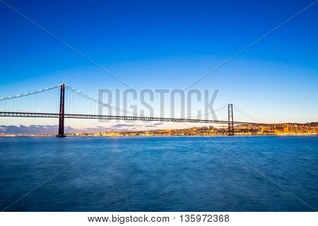 Lisbon cityscape with 25 de Abril suspension Bridge, Portugal at dusk
