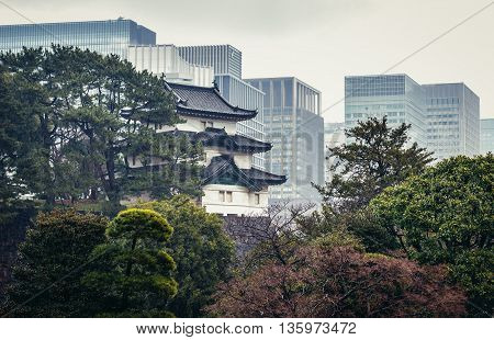 Tokyo Japan - February 26 2015: Fujimi yagura turret of Chiyoda Castle at Imperial Palace area with modern office buildings on background