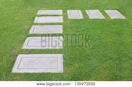 L shape of gravel pathway on green field as background