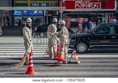 Tokyo Japan - February 27 2015: Group of men cleans street in Marunouchi area of Tokyo