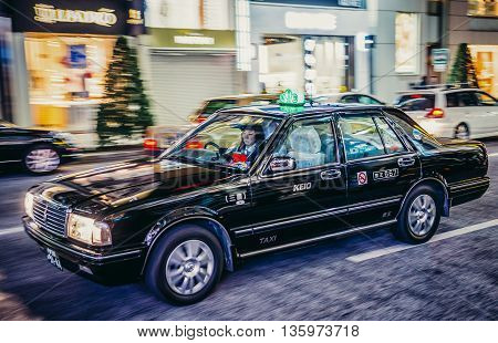 Tokyo Japan - February 27 2015: Woman drives typical Toyota cab on the street of Ginza district in Tokyo