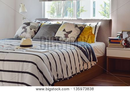 Stylish Bedroom Interior With Black And White Patterned Pillows On Bed And Decorative Table Lamp.