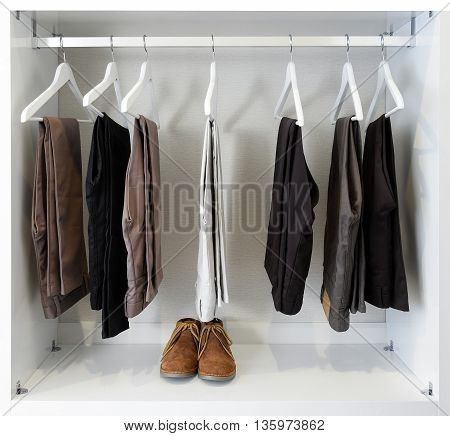 Brown Leather Shoes And Row Of Black Pants Hangs In Wardrobe
