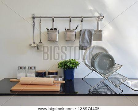 Modern Ceramic Kitchenware And Utensils On The Black Granite Counter Top