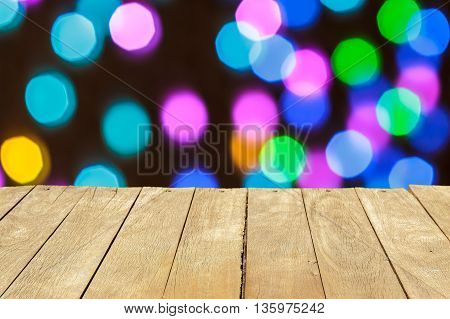 Empty wooden table or plank with colorful bokeh of light from building on background for product display.