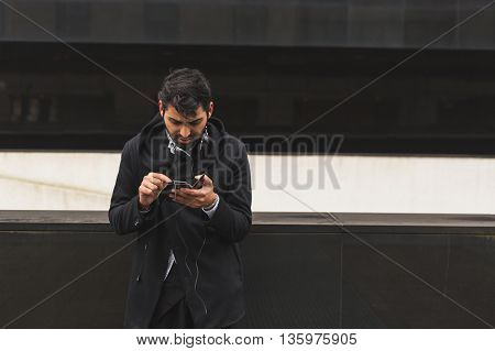 Handsome Indian Man Texting In An Urban Context