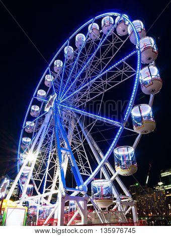 Amusement park attractions. Ferris wheel at night