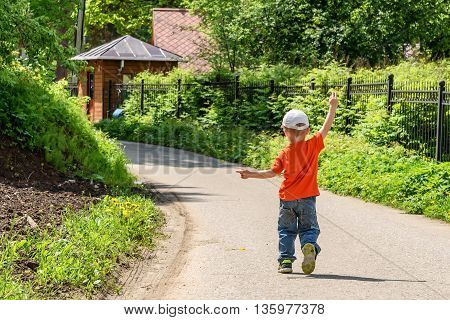 A little boy in an orange shirt and jeans walking along a path in a park