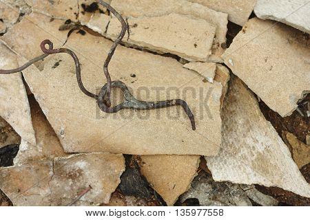 burned forged hook on broken roofing slate close up