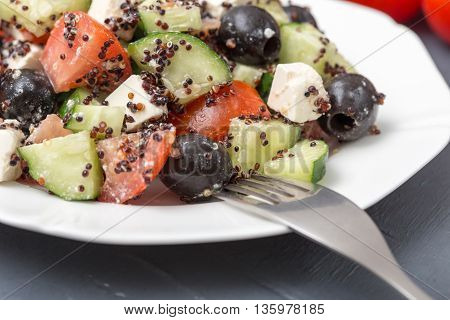 Fresh salad with black quinoa tomatoes cucumbers and feta cheese.