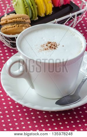 White cup of fresh cappuccino and sweet macaroons for morning coffee times.