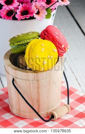 Sweet and colorful french macaroons or macaron in small wooden tank on wooden background Dessert.