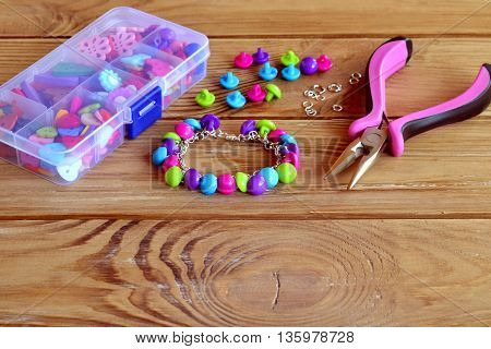 Colorful button charm bracelet, a box of different buttons, pliers, metal connecting rings on wooden table. Using buttons for original fun project. Easy make a bracelet. Hand jewelry