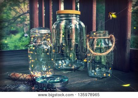 Fireflies in jars in a tree house, with magnifying glass. Long exposure, focus on top of jar on the left