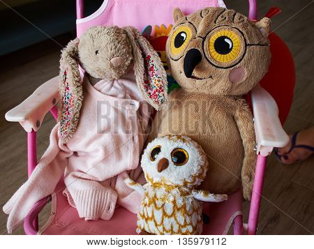 Soft stuffed animal toys in a child's bedroom on a pink chair