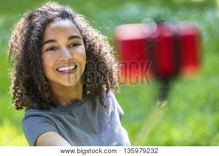 Beautiful happy mixed race African American young woman girl teenager female child smiling with perfect teeth taking selfie photograph with red cell phone on selfie stick