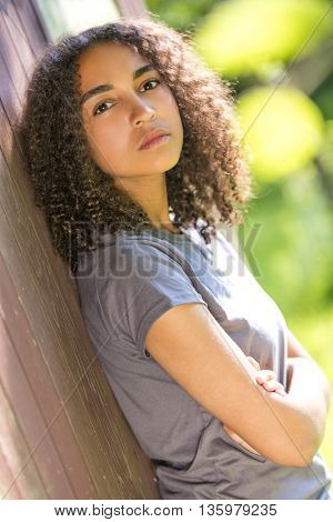 Beautiful mixed race African American girl teenager female young woman outside, arms folded in spring or summer looking sad depressed or thoughtful