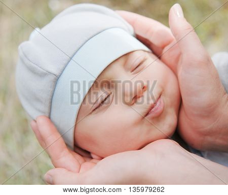 mother's hands gently hold the head of her small baby