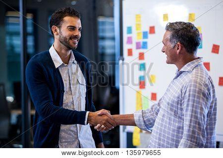 Businessmen having a handshake in office