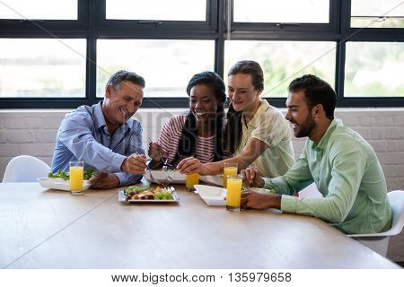Smiling team of business people having lunch in modern studio
