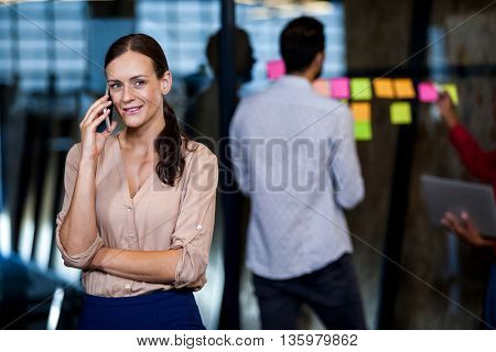 An attractive businesswoman having a phone call while colleagues have meeting in studio
