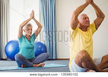 Side view of seniors doing yoga in studio