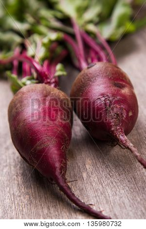 two fresh ripe beet on wooden background in studio