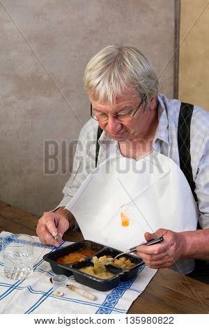 Elderly man in nursing home disliking his ready made dinner