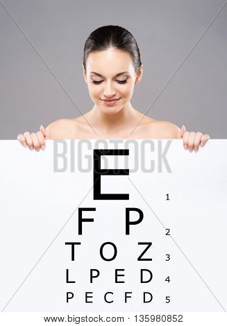 Attractive woman with a banner of test vision table over grey background.