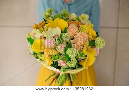 girl holding Bouquet of the different mixed orange flowers in woman hands