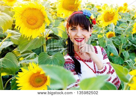Beautiful young girl in national ukrainian blouse embrodery looking to camera on a sunflower field at sunset backlight.