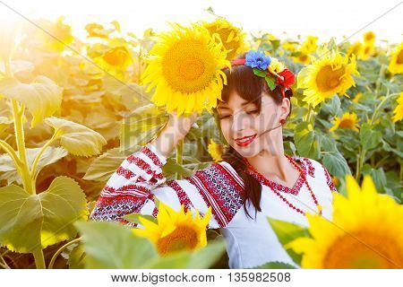 Beautiful young girl in national ukrainian blouse embrodery with closed eyes on a sunflower plant at sunset backlight.