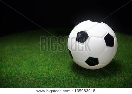 soccer ball on the green field with dark background