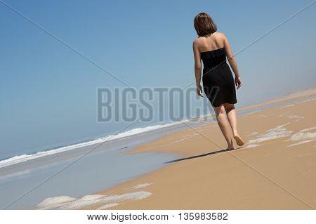 Lonely Girl Is Walking Along Coastline, Reflection On Wet Sand.