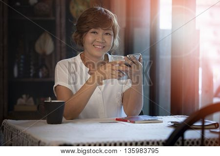 portrait of beautiful smiling face with happiness 40s years woman and smart phone in hand toothy smile