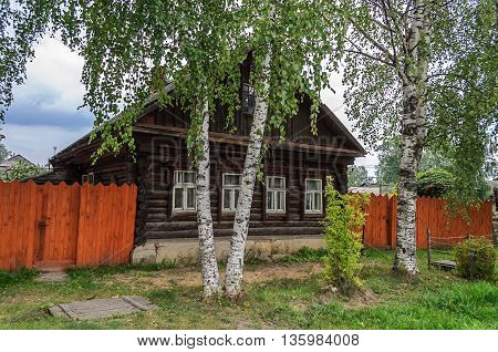 Old wooden country house with birches in front summer day