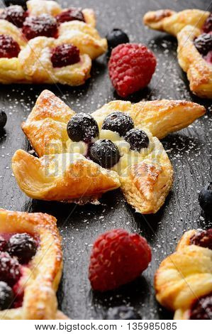 Puff pastries with raspberries, blueberries and cream cheese on black  background.