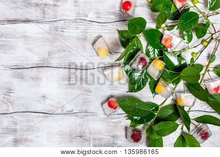 Cherry in ice cube with branch on white painted wood texture as background, top view