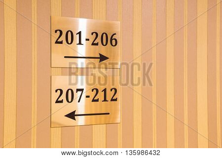 Gold metallic hotel sign with room numbers and arrows pointing in two opposite directions showing the way on a wall with striped plakpapier in a concept of travel