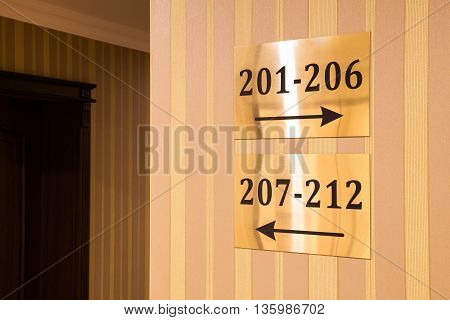 Gold colored hotel sign showing room numbers with two arrows pointing opposite directions showing which passage to follow conceptual of travel and tourism