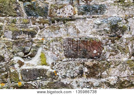 Stone wall with irregular shaped stones weather and old with small patches of moss