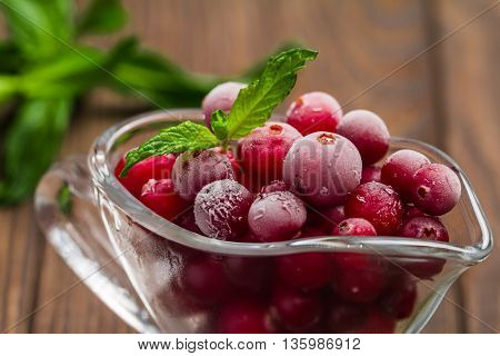 Frozen cranberries in a glass bowl on wooden background