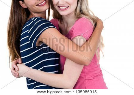 Happy female friends hugging on white background