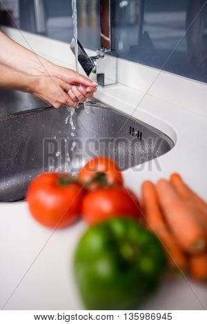 Cropped image of woman washing hands in sink at kitchen counter