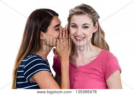 Woman telling secret to friend while standing on white background