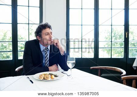 Thoughtful businessman sitting at table in restaurant