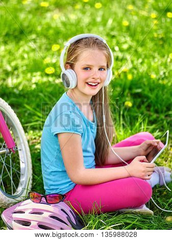 Bikes cycling girl. Girl rides bicycle. Girl wearing headset watching at tablet pc in cycling. Cycling is good for health. Cyclist looking at touch screen.
